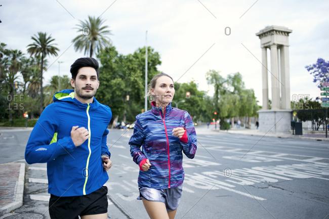 Joggers run on a city street
