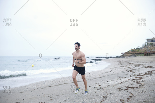 A man jogs on the beach with a heart rate monitor