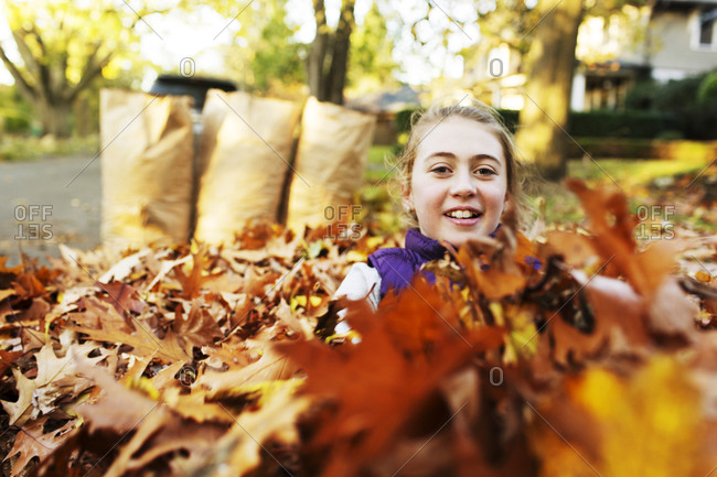 Girl covered with dry leaves