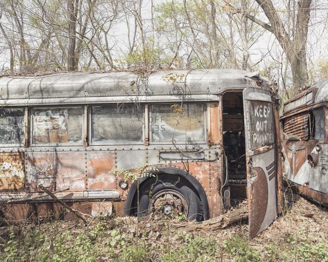 Decaying bus in a junkyard