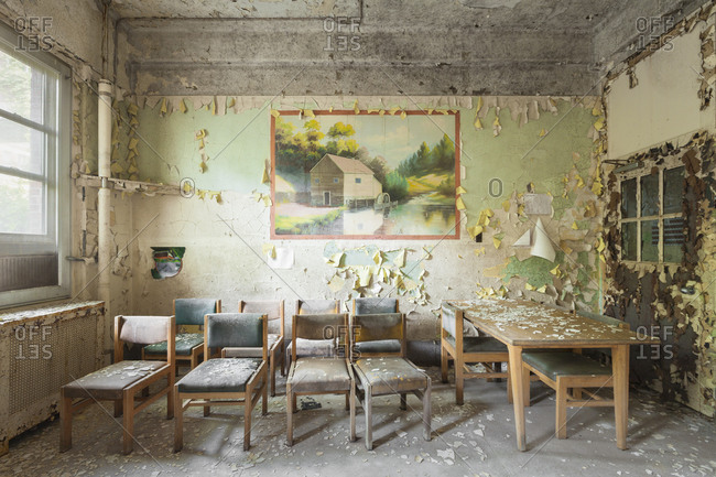 Tables and chairs left behind in a craft room inside an abandoned mental hospital