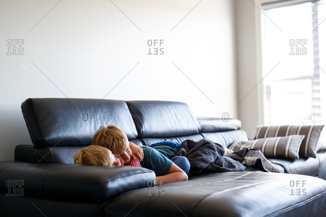 Siblings cuddling on a couch