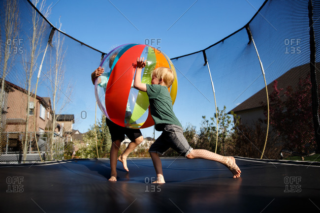 Children on a trampoline with a ball