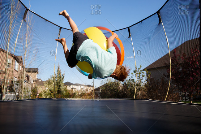 Boy playing on a trampoline with a ball