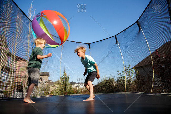 Children on a trampoline playing with a ball