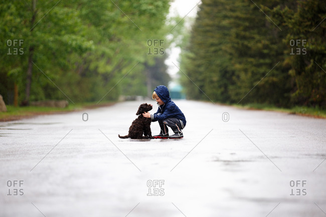 Boy with his puppy in the rain