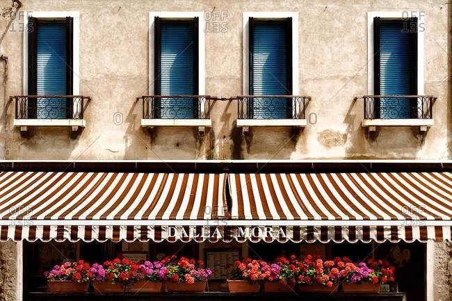 Facade of building with striped awning below windows and geraniums in planters