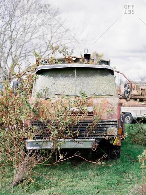 Discarded old van rusting in junkyard