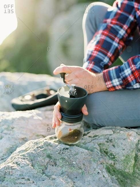 Grinding coffee beans outdoors on rocks