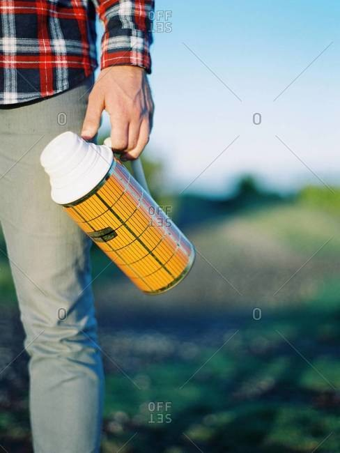 Man carrying a vintage thermos