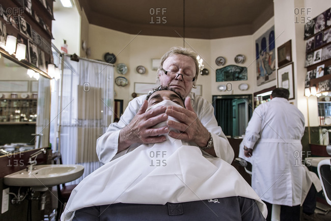 Milan, Italy - May 16, 2015: Barber treating his client to hot towel service for his beard