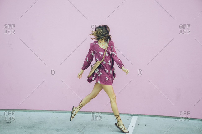 Woman skipping along pink colored wall in a purple dress and sandals