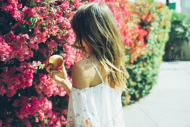 Woman eating an apple in front of a bougainvillea hedge