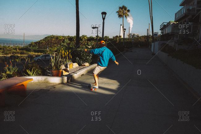 Man riding skateboard along a sidewalk in a coastal town