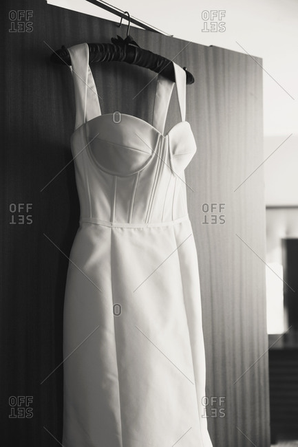 Close up of wedding dress hanging on a door
