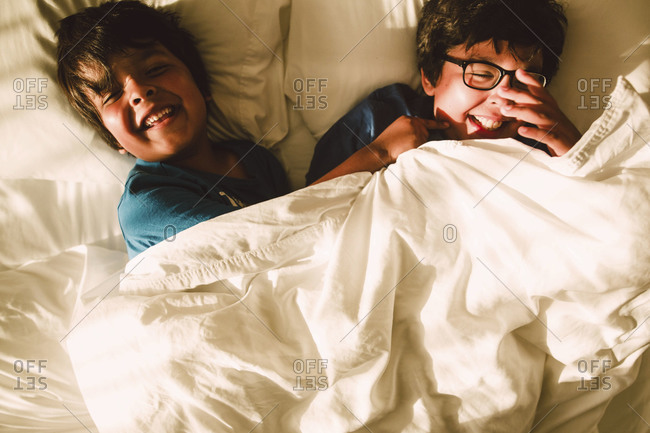 Two boys giggle in bed