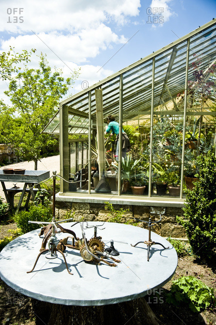 A woman works in a greenhouse on an estate