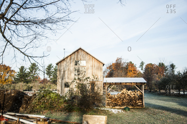 A woodshed next to a renovated barn made with mushroom wood siding