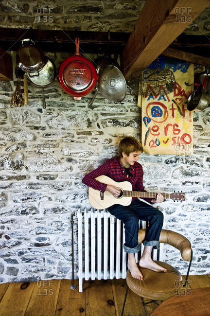 Accord, NY - October 31, 2011: A boy practices paying his guitar in a renovated farmhouse