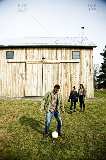 Accord, NY - October 31, 2011: A family plays soccer in front of a renovated barn