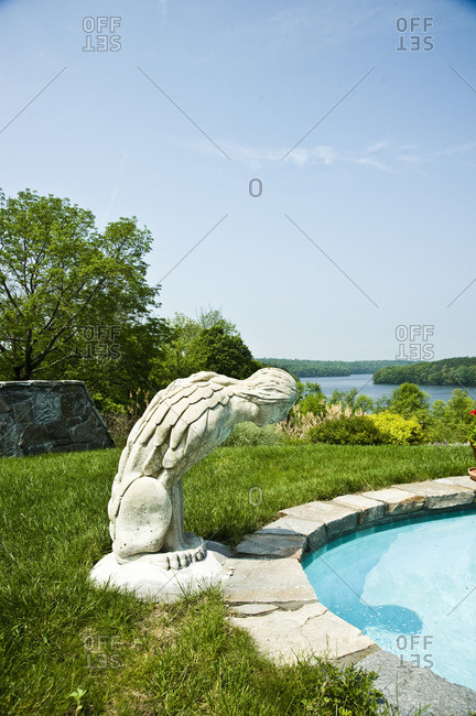 A sphinx sculpture pending over a pool