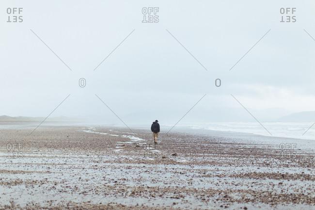 Young man walks on foggy beach in coastal Ireland