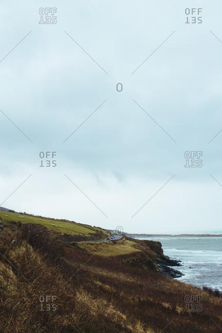 Cars drive along coastal road in Ireland