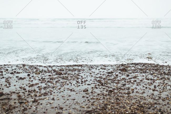 Rocks wash ashore on foggy beach in coastal Ireland