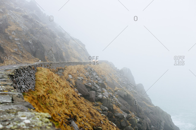 Cars drive on foggy road along cliffs in coastal Ireland
