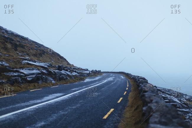 Fog rolls over cliffside road in coastal Ireland