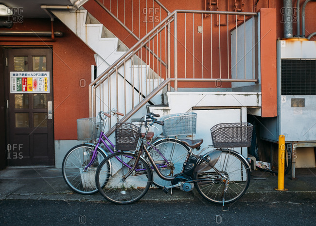Two bikes leaning against exterior steps