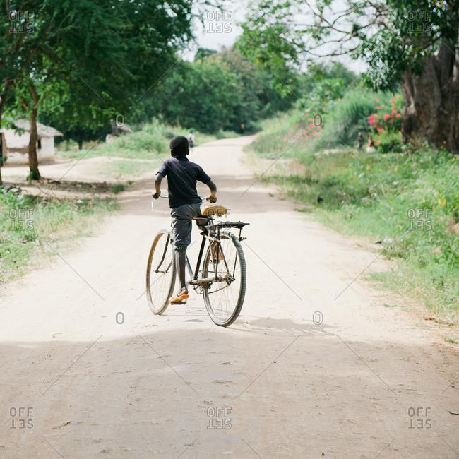 Boy riding a bike in Tanzanian village