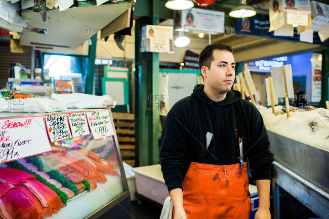 Seattle, WA, USA - May 22, 2013: A fishmonger at his stand at Pike Place Market in Seattle, WA