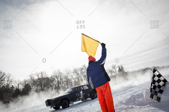 Hustisford, WI, USA - February 15, 2015: Man signaling with flag during winter lake race