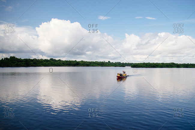 Men on small boat travel the Rio Negro river in Brazil