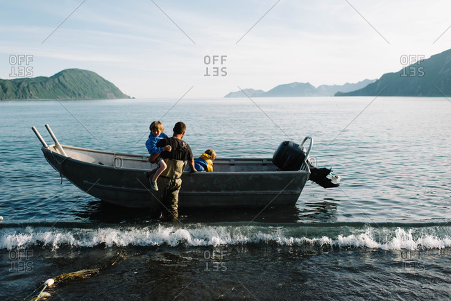 Man helping children out of a fishing boat