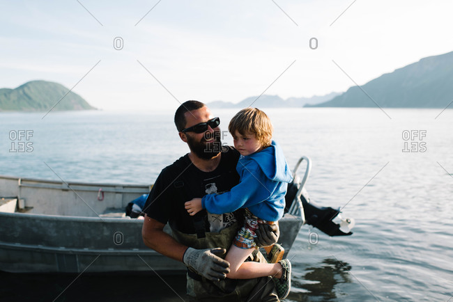 Fisherman carrying child ashore - Offset