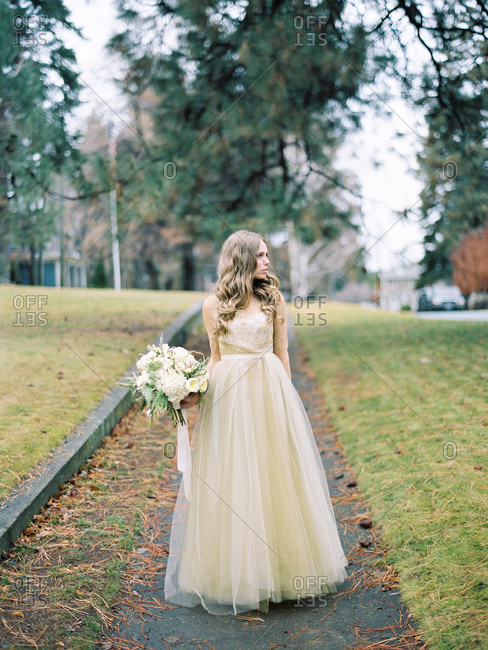 Bride standing on wet fall street looking to the side