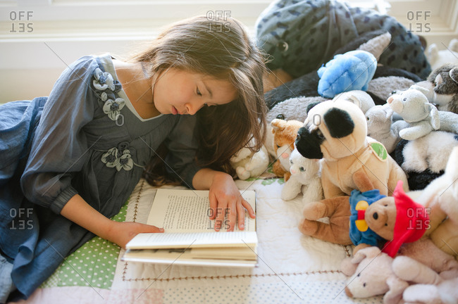 Young girl reading a book on her bed to an audience of stuffed animals