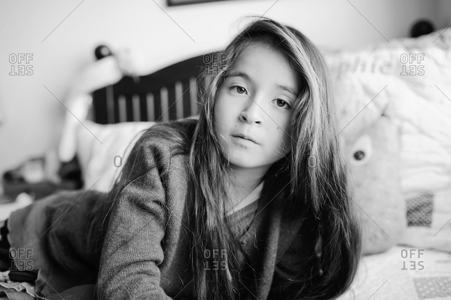 Preteen girl lying on her bed