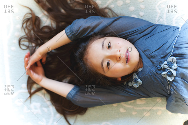 Girl lying on her back with her hair spread out and arms stretched overhead