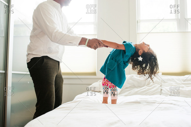 A daughter plays with his daughter on a bed