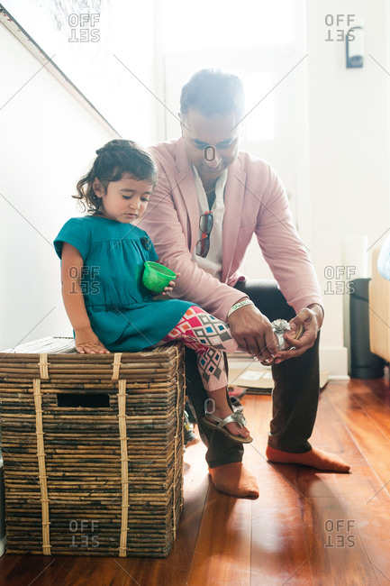 A father puts shoes on his daughter