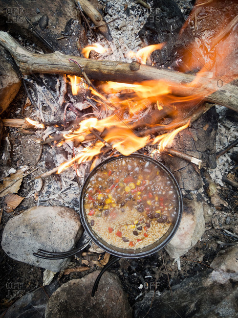 Pot of soup over campfire flames