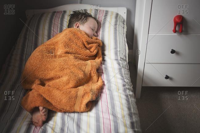 Young boy asleep under a towel