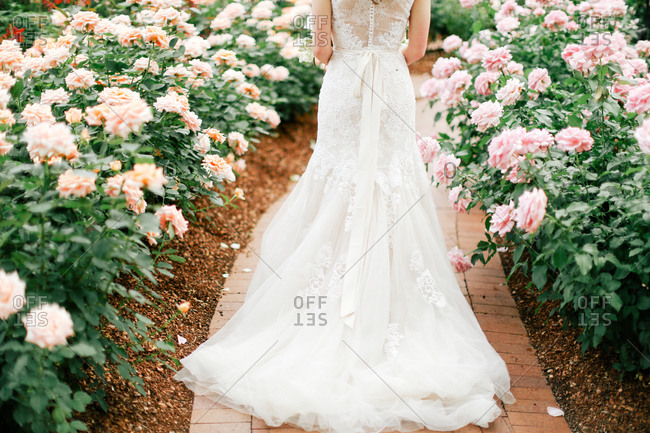 A bride walks down a brick path