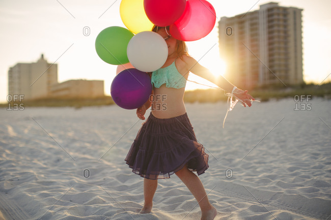 Girl walking on beach carrying balloons