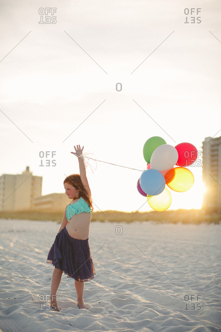 Girl dancing on beach with balloons