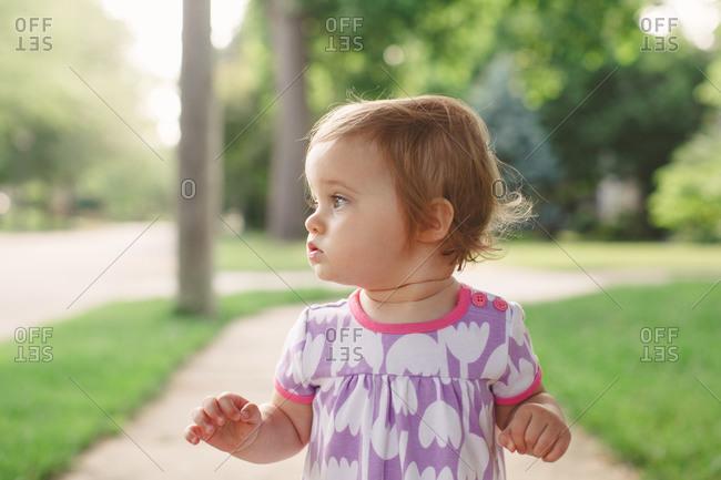 Toddler girl on summer sidewalk staring off