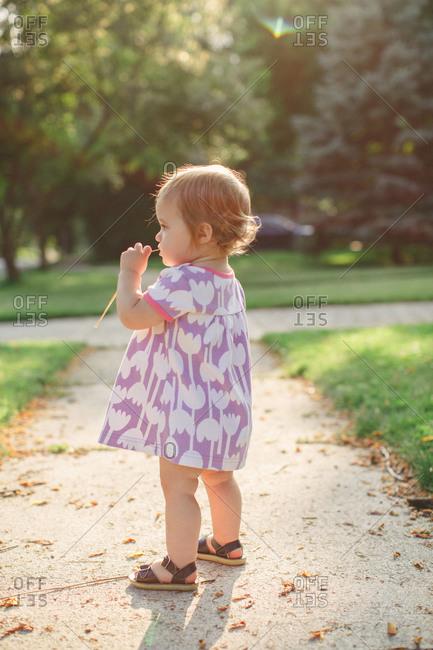 Toddler girl standing on sidewalk staring off